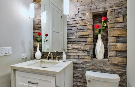 white vanity powder room with stone wall
